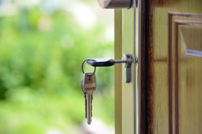Keys opening a door to newly purchased home with a real estate title